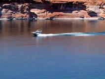 一条快行小船在湖鲍威尔把苏醒留在幽谷峡谷全国度假区 库存照片