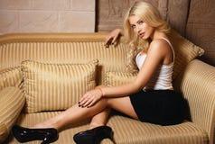 一条性感的黑裙子的美丽的白肤金发的女孩 免版税图库摄影