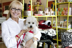 一条愉快的资深妇女运载的狗的画象在宠物店的 库存图片