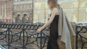 一条时兴的鸡尾酒连衫裤的美丽的女孩沿一个城市堤防去在slo mo 影视素材