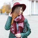 一条时髦的帽子和围巾的美丽的女孩反对白色buil 库存图片