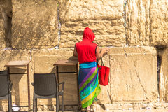 一条明亮的红色夹克和五颜六色的女性围巾的未认出的游人,怀有腿简而言之在西部墙壁 免版税库存图片