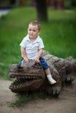 一条木鳄鱼的小男孩 免版税库存照片