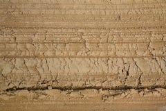 一条未铺砌的含沙沃土的路的片段的Macrophoto有平地机的踪影的 免版税库存图片