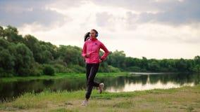 一条桃红色夹克和黑裤子的一个女孩在耳机的河附近跑为马拉松做准备 影视素材