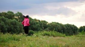 一条桃红色夹克和黑裤子的一个女孩在耳机的河附近跑为马拉松做准备 股票录像