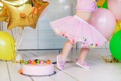 一条桃红色蓬松裙子的小女孩 与五颜六色的球的桃红色奶油甜点蛋糕在一个白色木地板上 免版税库存照片