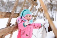 一条桃红色连衫裤的女孩在一个多雪的冬天公园走 库存照片