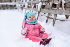 一条桃红色连衫裤的女孩在一个多雪的冬天公园走 免版税库存照片