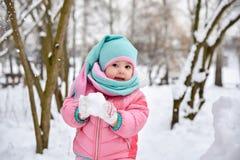 一条桃红色连衫裤的女孩在一个多雪的冬天公园走 库存图片