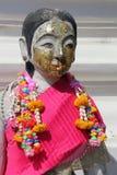 一条桃红色围巾和花诗歌选装饰神(泰国)的雕象 免版税库存图片