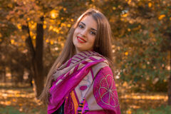 一条桃红色围巾的美丽的女孩在秋天公园站立并且微笑 免版税库存图片