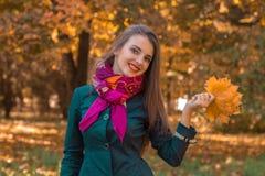 一条桃红色围巾的逗人喜爱的女孩在她的脖子上在秋天公园站立并且保持叶子手中 免版税库存图片