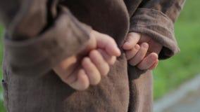 一条棕色亚麻制连衫裤的小婴孩阻挡他的在他后的手 股票录像