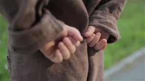 一条棕色亚麻制连衫裤的小婴孩阻挡他的在他后的手 影视素材