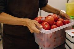 一条棕色围裙的男性厨师在有红色蕃茄篮子的厨房里在他的手上 烹调的过程在厨房里 图库摄影