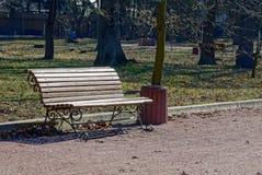 一条棕色长凳在公园和缸 免版税库存图片