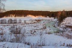 一条河和小山的冬天风景在雪,一个冷的季节和一条蓝色涌现的河乌拉尔的 免版税库存图片