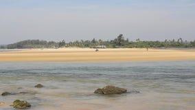 一条河的流程有石头在水中以一个黄色沙滩为背景和绿色密林的在天空蔚蓝下和 股票录像