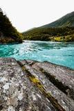 一条河的绿松石水有岩石、峭壁和树的在背景中在挪威 免版税库存图片