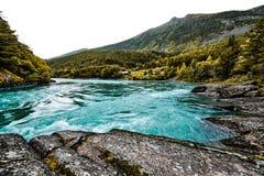 一条河的绿松石水有岩石、峭壁和树的在背景中在挪威 免版税库存照片