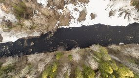 一条河的鸟瞰图在有雪的森林里沿银行 免版税库存照片