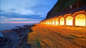 一条沿海高速公路的风景由多岩石的海滩的在与光的日出前从岩石流洒了照亮海岸的隧道 免版税库存图片