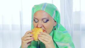 一条浅绿色的围巾的一名年轻回教妇女在咖啡馆吃一个汉堡 股票视频