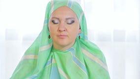 一条浅绿色的围巾的一名年轻回教妇女在咖啡馆吃蛋糕并且喝茶 股票视频