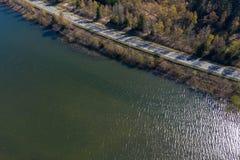 一条涂柏油的乡下公路的鸟瞰图沿一座密集地树木繁茂的山的边缘的在水坝的银行的 库存图片