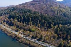 一条涂柏油的乡下公路的鸟瞰图沿一座密集地树木繁茂的山的边缘的在水坝的银行的 免版税图库摄影