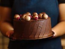 一条深蓝围裙的一名妇女拿着巧克力饼用莓和黑醋栗在被弄脏的背景 免版税图库摄影