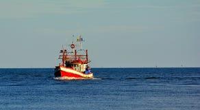 一条渔夫小船在海蓝天背景中 库存照片