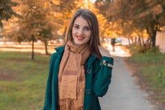 一条温暖的围巾的微笑的女孩在看起来的街道上站立不错和 免版税库存图片