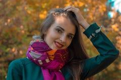一条温暖的围巾的美丽的女孩保留您的头发和微笑的特写镜头的手 库存照片