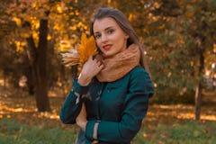 一条温暖的围巾的逗人喜爱的女孩在他的手上拿着枫叶并且微笑 库存图片