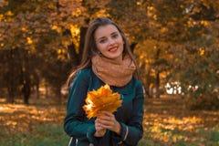 一条温暖的围巾的逗人喜爱的女孩对叶子看起来平直和微笑负 免版税库存照片