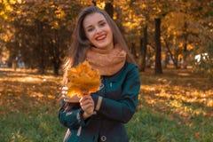 一条温暖的围巾的年轻快乐的女孩在脖子举行叶子和微笑 免版税库存图片