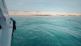 一条游艇在有人的海洋在船上 以一个岩石沙漠海滩为背景 潜水和渔侧视图 股票视频