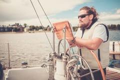 一条游艇的上尉在方向盘后 免版税库存照片