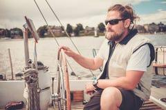 一条游艇的上尉在方向盘后 免版税库存图片
