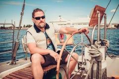 一条游艇的上尉在方向盘后 库存照片