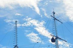 一条游艇的两帆柱有索具的看反对与白色云彩的蓝天 免版税图库摄影