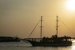 一条游艇的剪影在反对落日的海 在游艇上是人剪影  库存图片