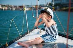 一条游艇的滑稽的小男孩上尉在夏天 库存图片