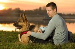 一条漂亮的孩子、父亲和狗的画象在日落 库存照片