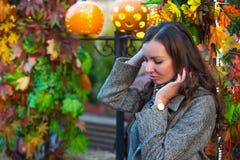 一条灰色外套和色的围巾的一名妇女在秋天在莫斯科 免版税库存照片
