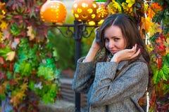 一条灰色外套和色的围巾的一名妇女在秋天在莫斯科 免版税库存图片