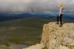 一条灰色hoody,黑长腿的一名年轻白肤金发的妇女在t站立 免版税库存照片
