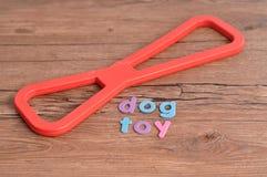 一条狗的一个红色橡胶拔河玩具与词狗玩具 免版税库存图片